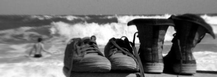 Kaksi paria kenkiä meren rannalla